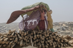 Balukhali-Kutupalong refugee camp, Ukhia subdistrict, Cox's Bazar, Bangladesh,19/03/2018 - Some rohingya sheltering from the wind and the sand in a makeshi  tent in Balhukali camp. With the deforestation implemented to set up the camps and to built the shelters now the soil is exposed to atmospheric agents and subject to a strong erosion which increases the risk of land sliding.